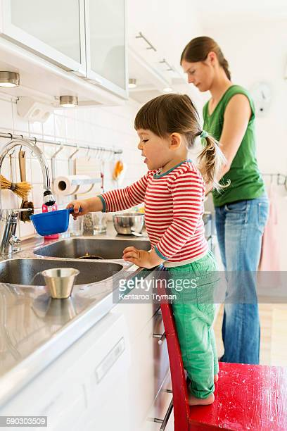 Side view of little girl filling water in container while standing on chair with mother in background at kitchen