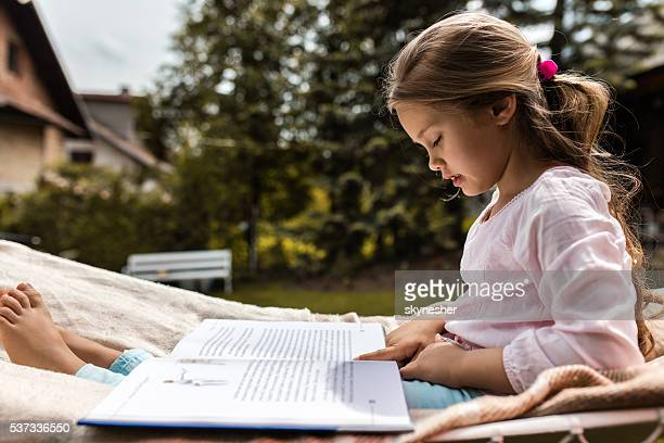 Side view of little girl reading a book in backyard.