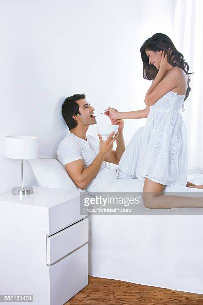 Side view of loving young woman feeding man in bed