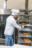Side view of male chef holding rack with loaves of bread