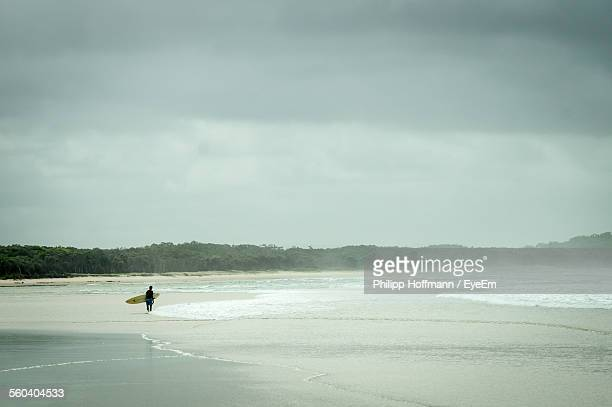 Side View Of Male Surfer Standing On Beach