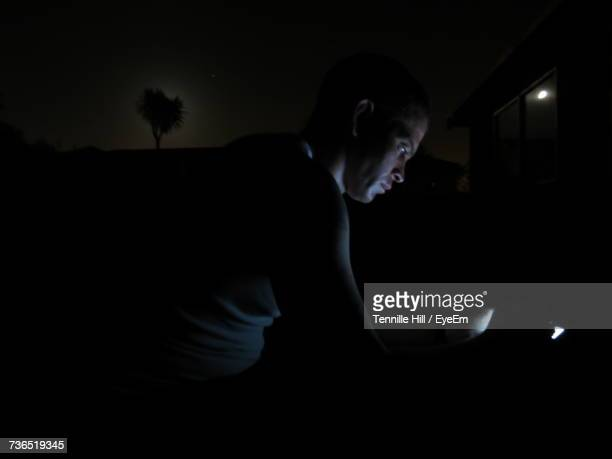 Side View Of Man By Glowing Light At Night