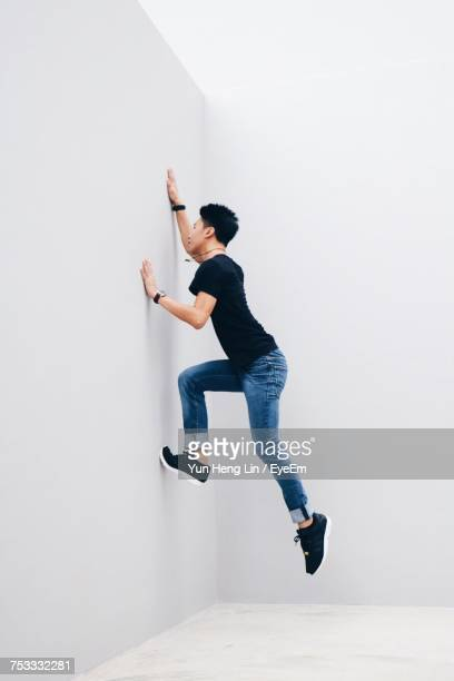 Side View Of Man Climbing White Wall