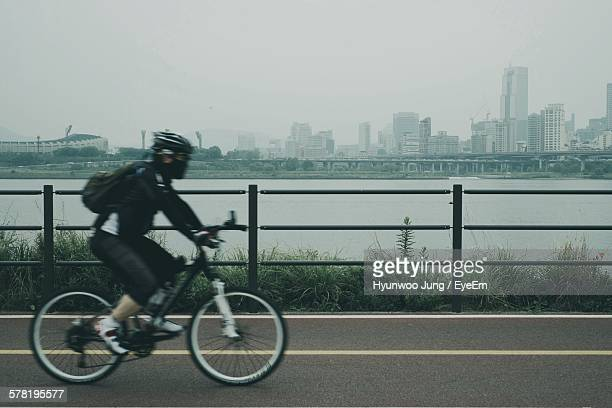 Side View Of Man Cycling On Bridge By Han River