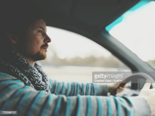 Side View Of Man Driving Car