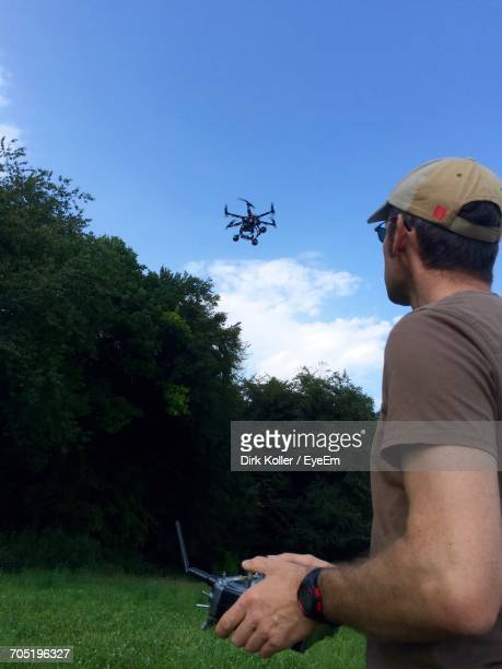 Side View Of Man Flying Drone At Park