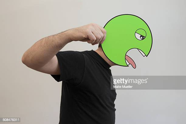Side view of man holding a green vomit emoticon face in front of his face