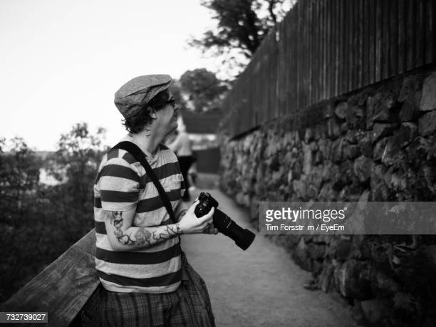 Side View Of Man Holding Camera While Leaning On Railing At Footpath