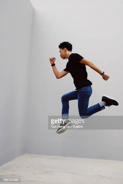 Side View Of Man Jumping Against White Wall