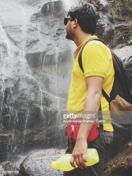 Side View Of Man Looking At Waterfall While Standing In Forest