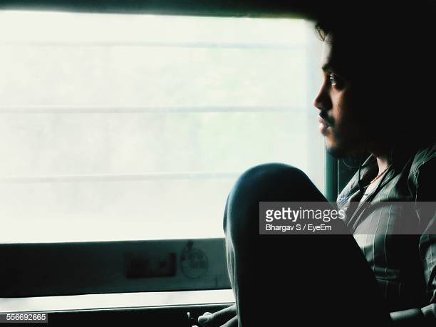 Side View Of Man Looking Out Of Train Window