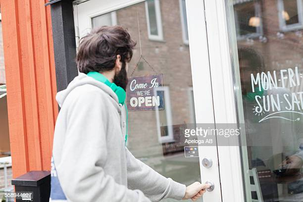 Side view of man opening cafe door