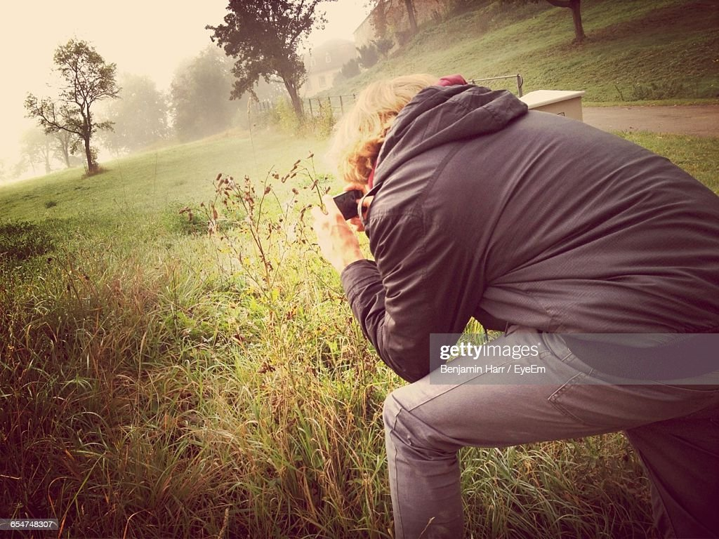 Side View Of Man Photographing On Grassy Field During Foggy Weather