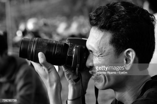 Side View Of Man Photographing Through Camera