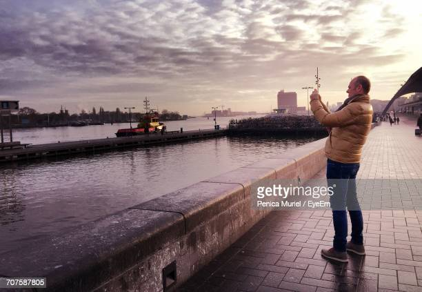 Side View Of Man Photographing While Standing By Lake