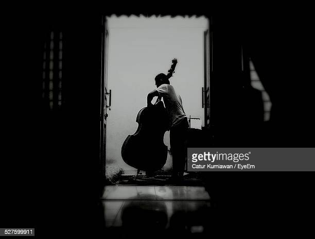 Side View Of Man Playing Cello At Home