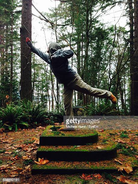 Side View Of Man Playing With Stick While Standing On One Leg In Forest
