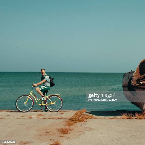 Side View Of Man Riding Bicycle Against Sea