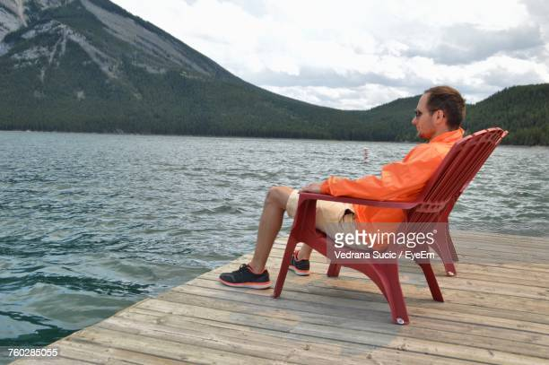 Side View Of Man Sitting On Red Adirondack Chair At Pier Over Lake