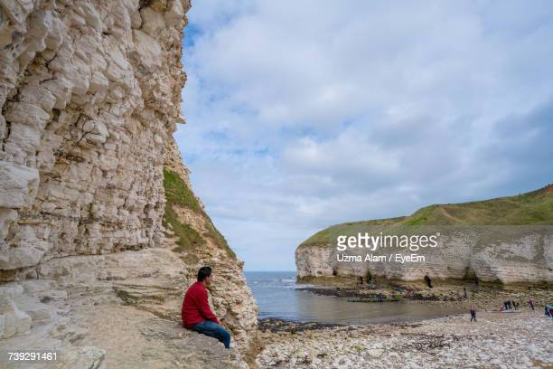 Side View Of Man Sitting On Rock At Beach Against Cloudy Sky