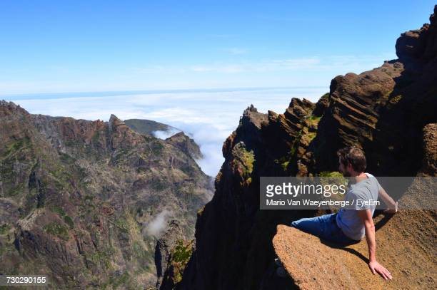Side View Of Man Sitting On Rock At Mountain Against Sky