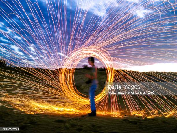 Side View Of Man Spinning Wire Wool Against Cloudy Sky
