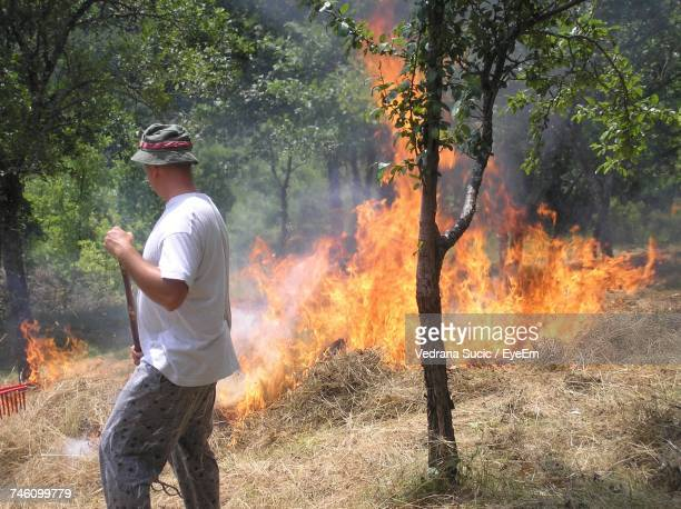 Side View Of Man Standing By Burning Hay At Forest