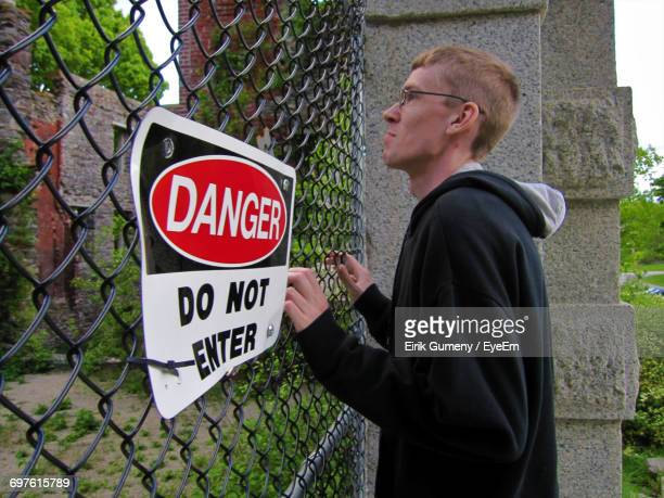 Side View Of Man Standing By Chainlink Fence With Do Not Enter Sigh Board