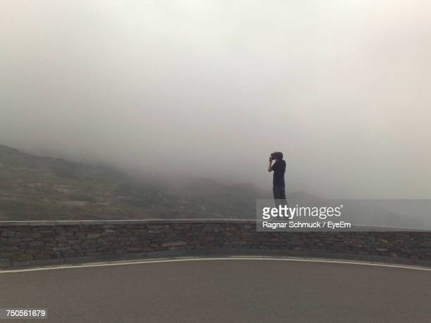 Side View Of Man Standing On Retaining Wall During Foggy Weather