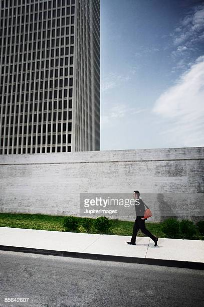 Side view of man walking by office building