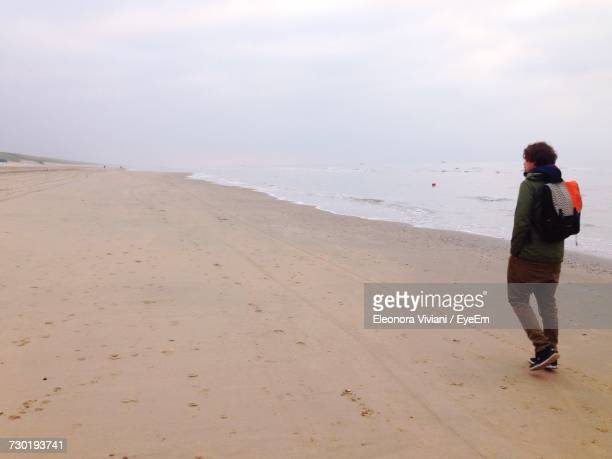 Side View Of Man Walking On Sand At Beach Against Sky