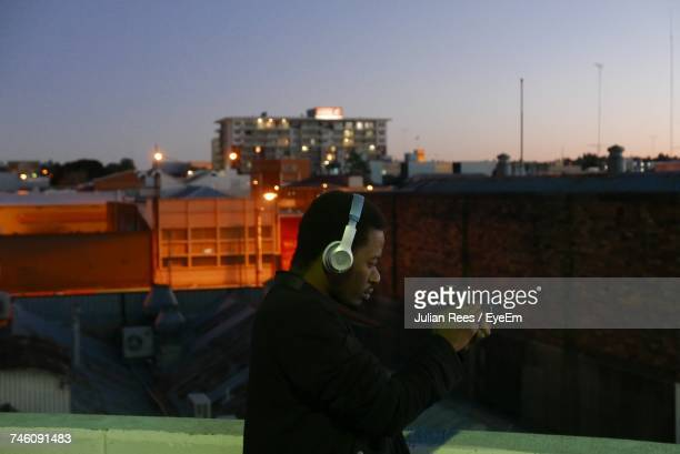 Side View Of Man Wearing Headphones While Photographing Through Digital Camera In City