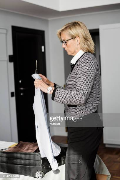 Side view of mature businesswoman holding blue shirt in coathanger at hotel room