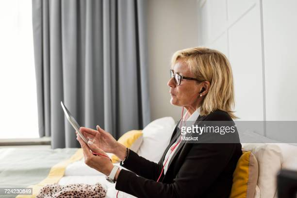 Side view of mature businesswoman using digital tablet sitting on bed at hotel room