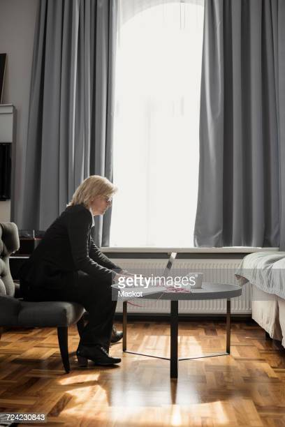Side view of mature businesswoman using laptop by window at hotel room