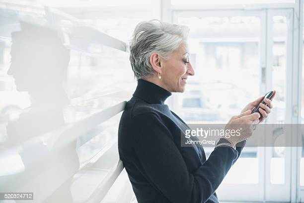 Side view of mature businesswoman using smartphone