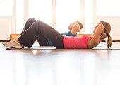 Side view of fit mature couple practicing sit-ups. Man and woman are practicing yoga at home. They are in sports clothing, in brightly lit apartment.