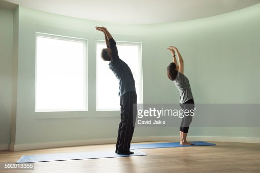 Side view of mature couple reaching upwards stretching arms bending backwards