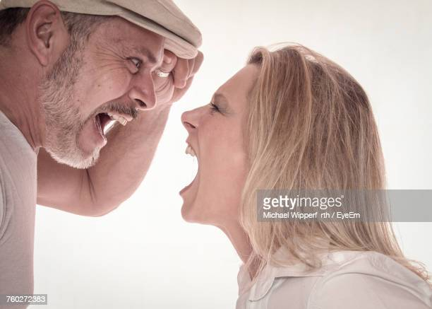 Side View Of Mature Couple Shouting Against White Background