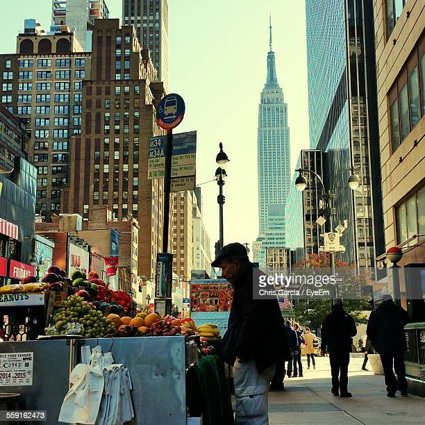 Side View Of Mature Man Buying Fruit At Street Market Against Empire State Building