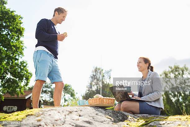 Side view of mature man talking to businesswoman using laptop on rock