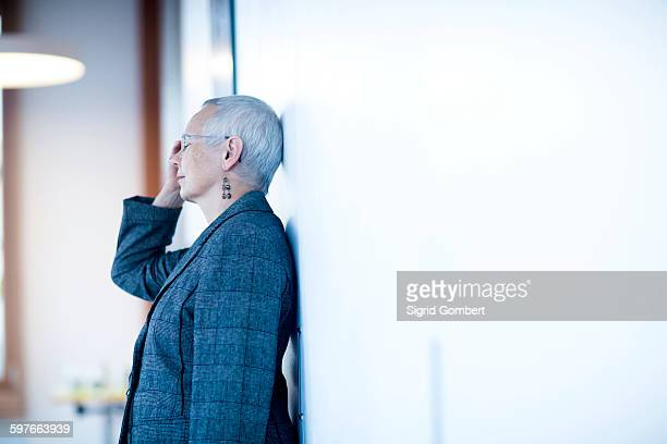 Side view of mature woman leaning against wall, hand on head, eyes closed looking stressed