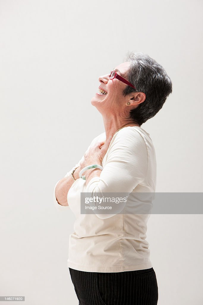 Side view of mature woman smiling, studio shot : Stock Photo