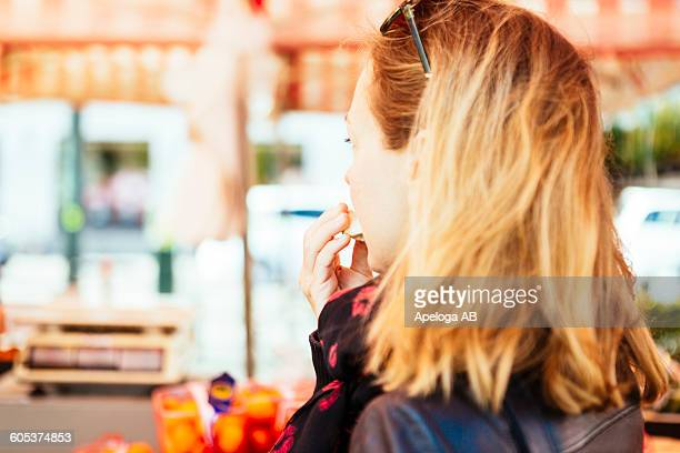 Side view of mature woman tasting fruit at market