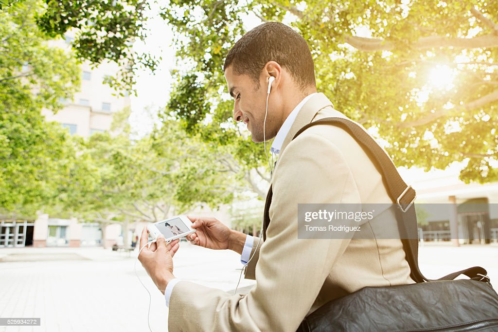 Side view of mid adult man holding phone and listening to music : Foto de stock