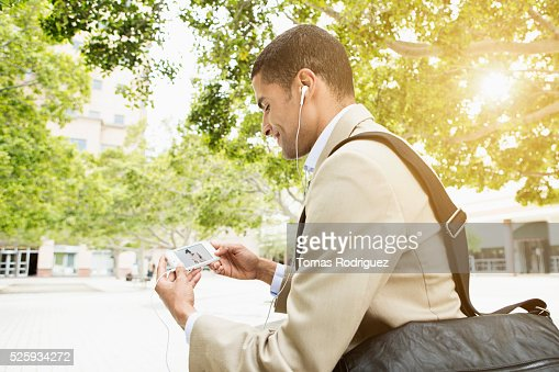 Side view of mid adult man holding phone and listening to music : Stock Photo