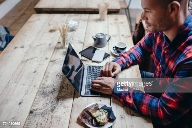 Side view of mid adult man using laptop at table in coffee shop