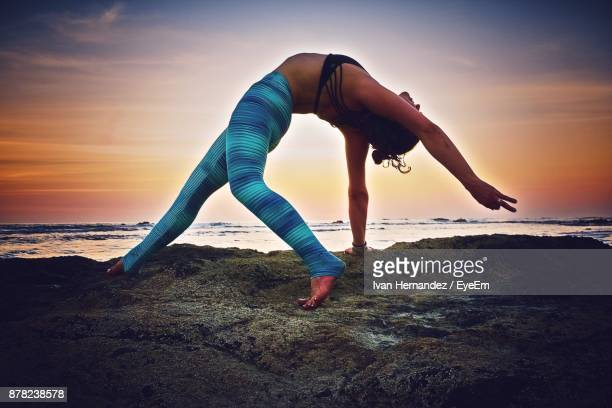 Side View Of Mid Adult Woman Exercising At Beach Against Sky During Sunset