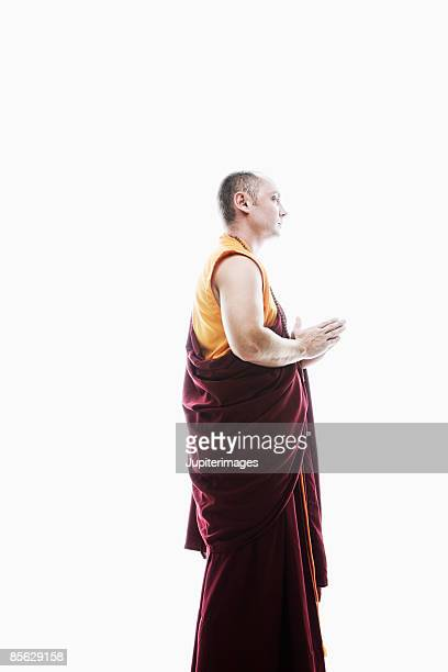 Side view of monk in prayer pose