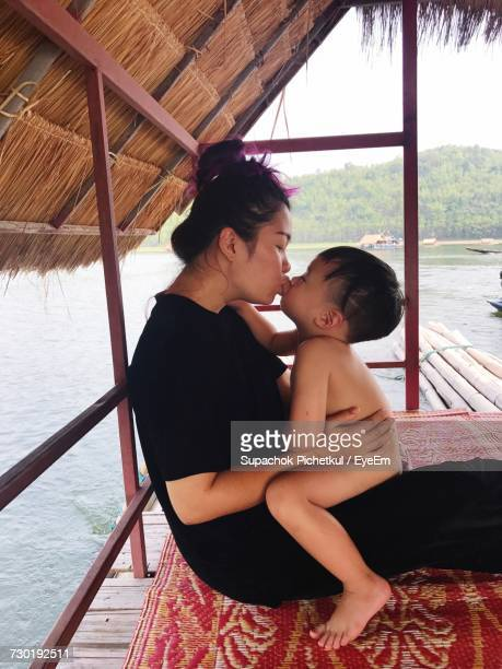 Side View Of Mother Kissing Son In Boathouse At Lake